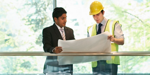Two men at a construction site looking at a set of blueprints.
