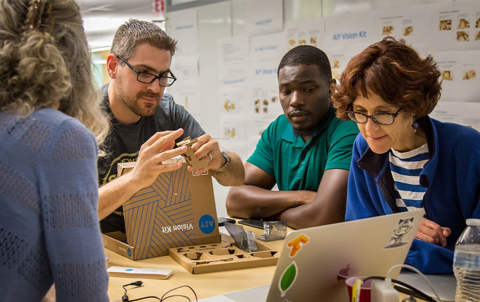 group of people at a table working on a technology project