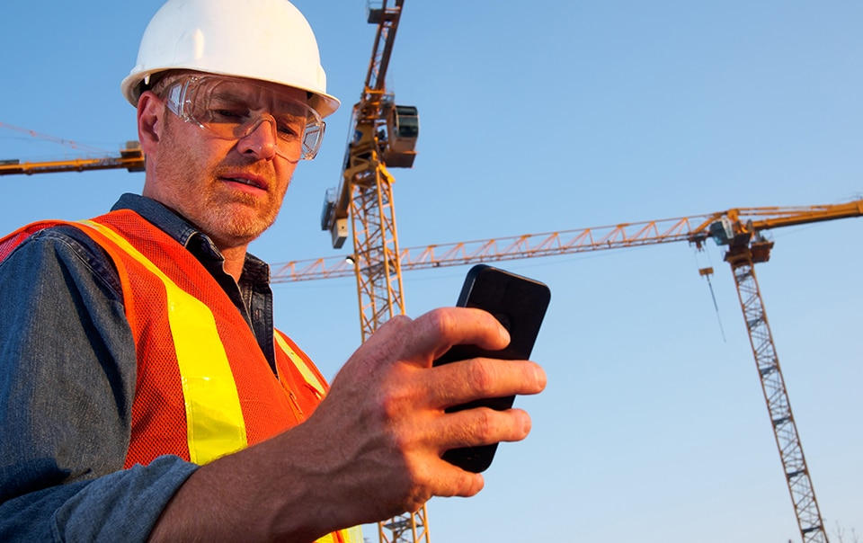 Construction worker checking vibration app on construction site