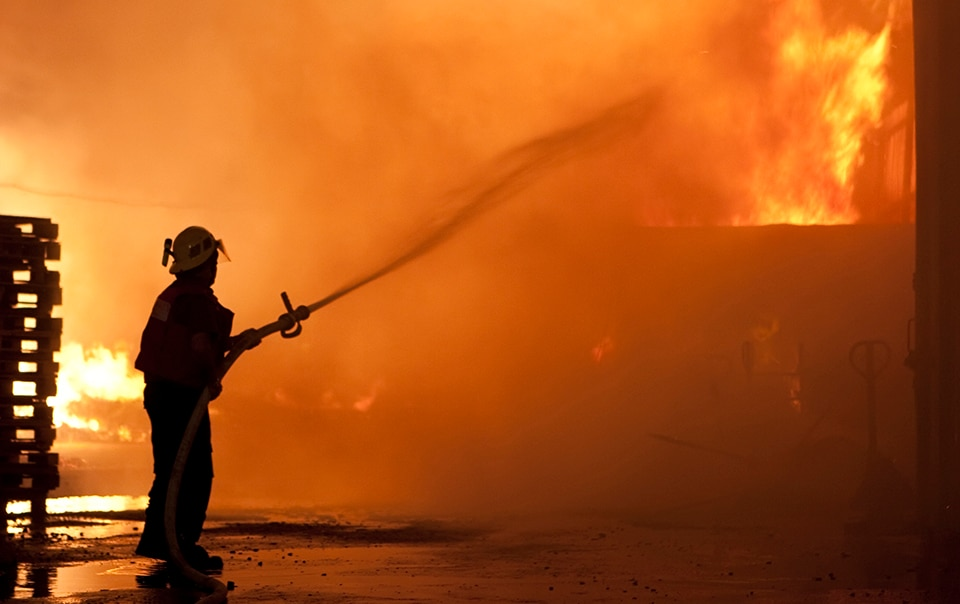 Fireman dousing wood-framed fire with water