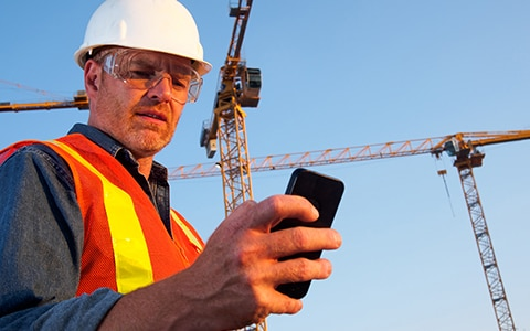 Construction worker using technology to identify risks