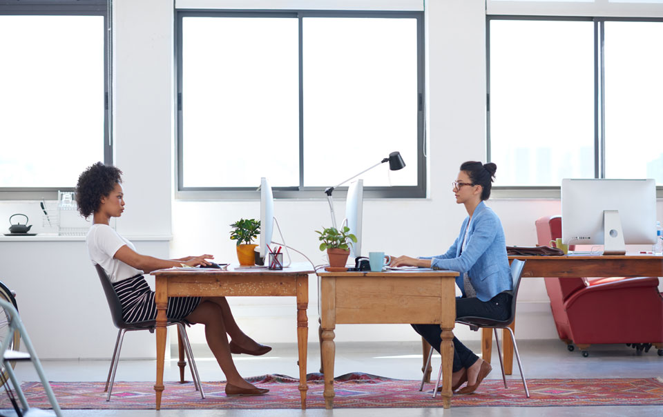 Two young professionals sitting at desks in open office
