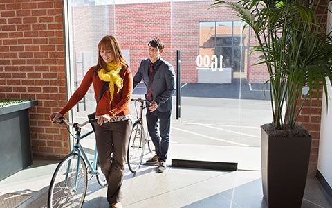 Two workers entering office with their bikes