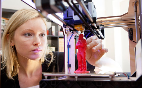 Woman reviewing 3D printed red figurine