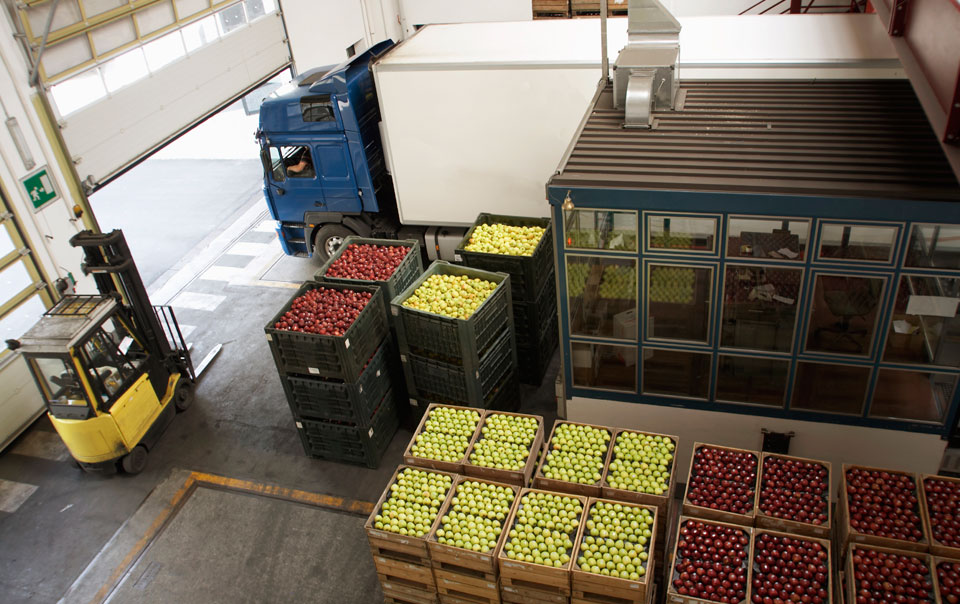 Truck driving next to open crates of fruit
