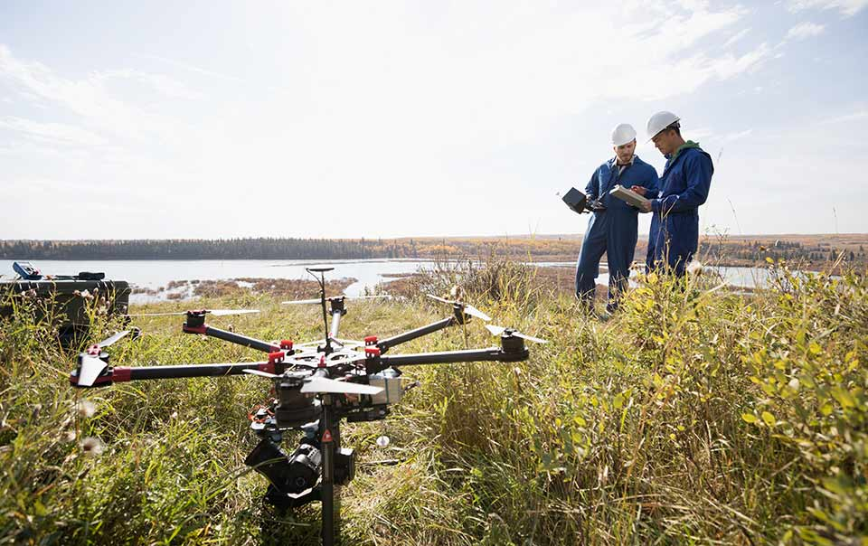 Two business workers operating drone in field