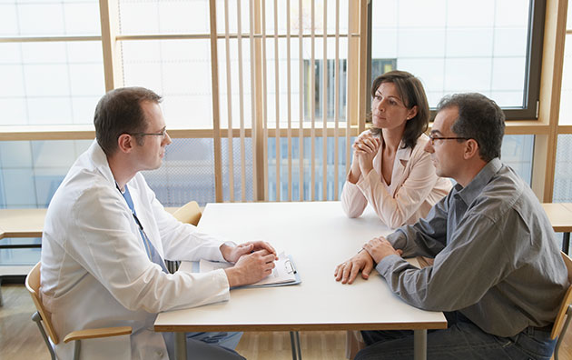 Doctor meeting with two professionals at a table