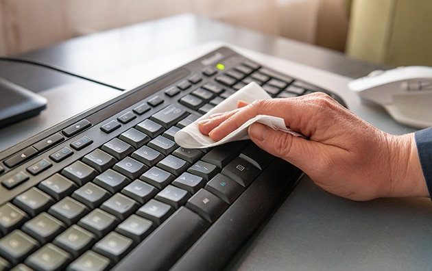 person at work cleaning their keyboard