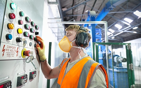 man in mask and gloves checking a control board