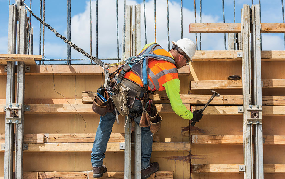 man with safety harness on at construction site