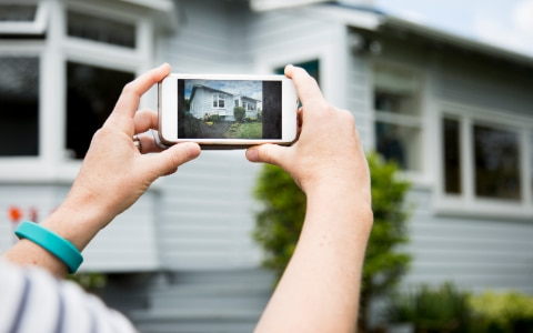 woman takes picture of house with smart phone