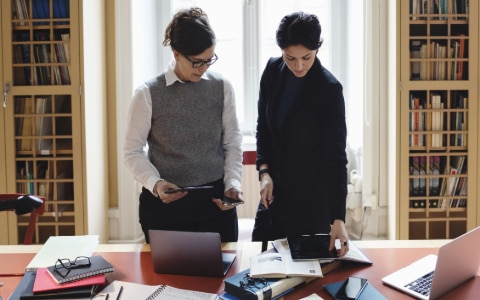 two women looking at paperwork
