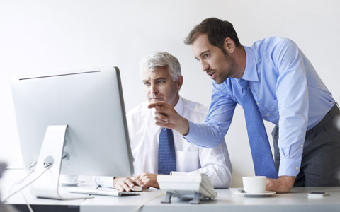 Two professionals looking at computer screen after a data breach