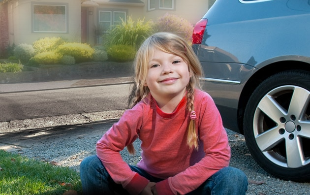 girl sitting in front of house and car