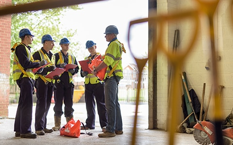 Construction Risk Management - construction workers standing in a circle in a warehouse of tools