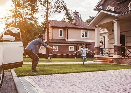 child running to father in front of car and home