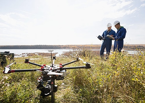 commercial employees using a drone to monitor farmland