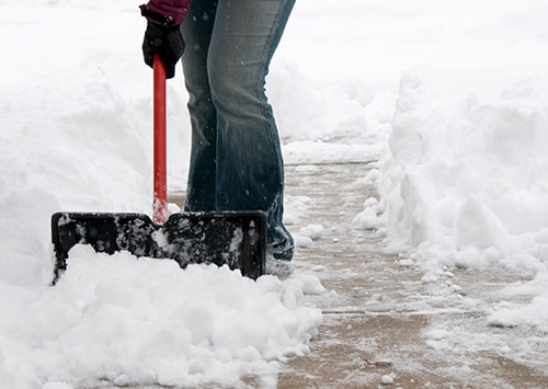 person shoveling sidewalk