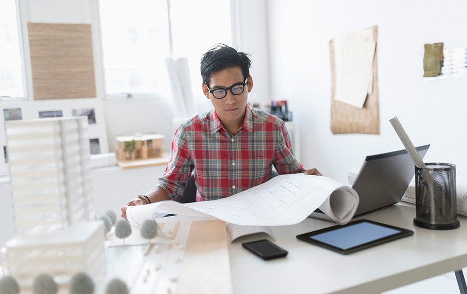 man looking at plans at his desk, design-build agreements: tips to help protect your design business