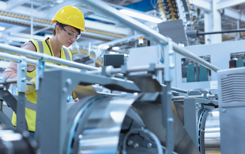 Woman looking at equipment in manufacturer