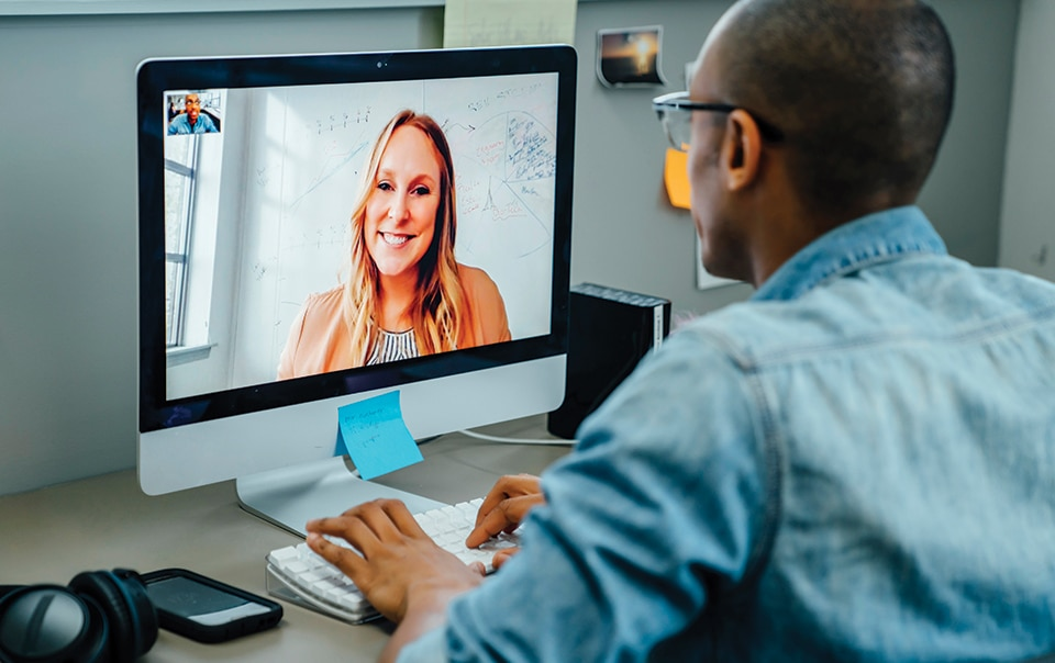 A man virtually conferencing with a woman using a desktop computer
