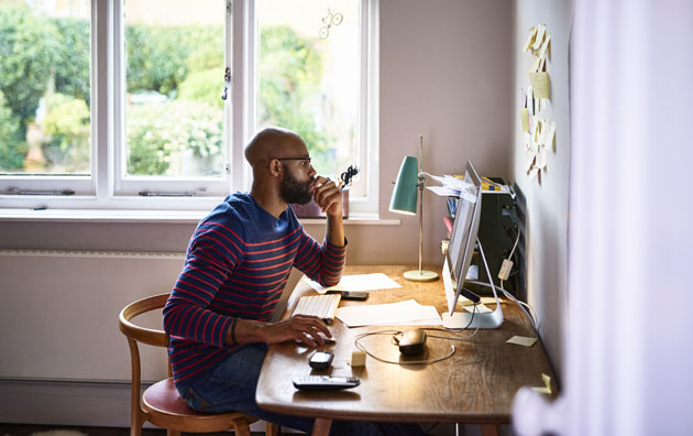 man sitting at desk working from home, Cybersecurity for Employees Working from Home