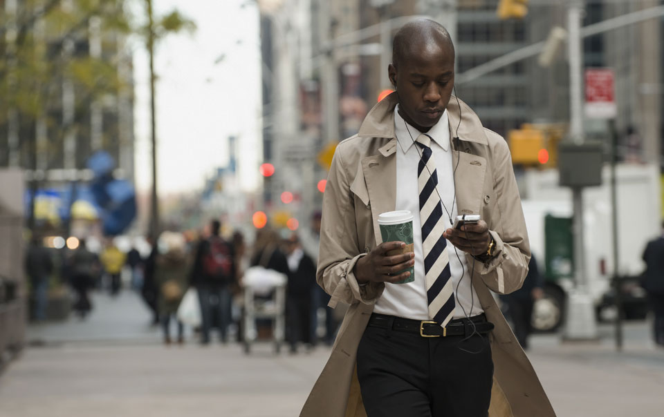 Professional using smartphone while walking on the street