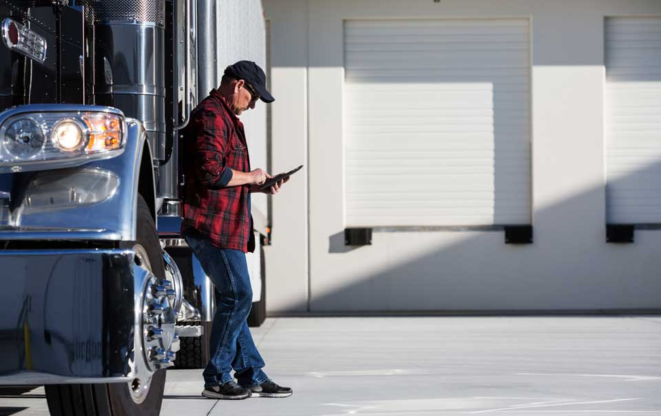 Truck driver looking at tablet next to truck