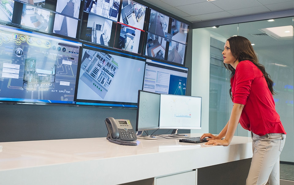 Woman in red top reviewing a screen of camera surveillance