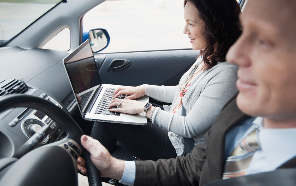 Professionals in car and passenger typing on laptop