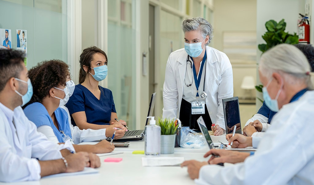 a medical professional standing in front of a table seated by other people in masks