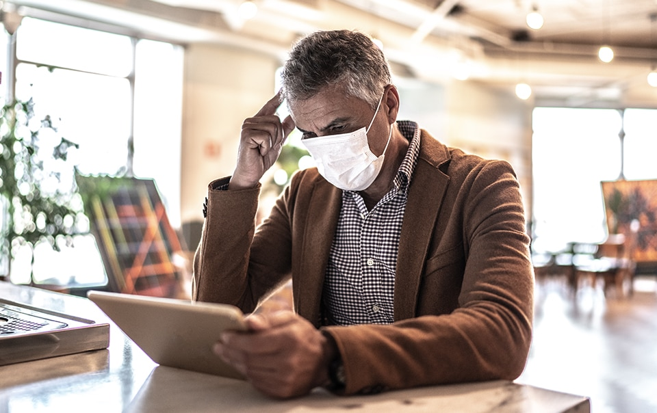 man sitting at table wearing a mask and looking at a tablet, Establishing and Managing Your COVID-19 Response Plan