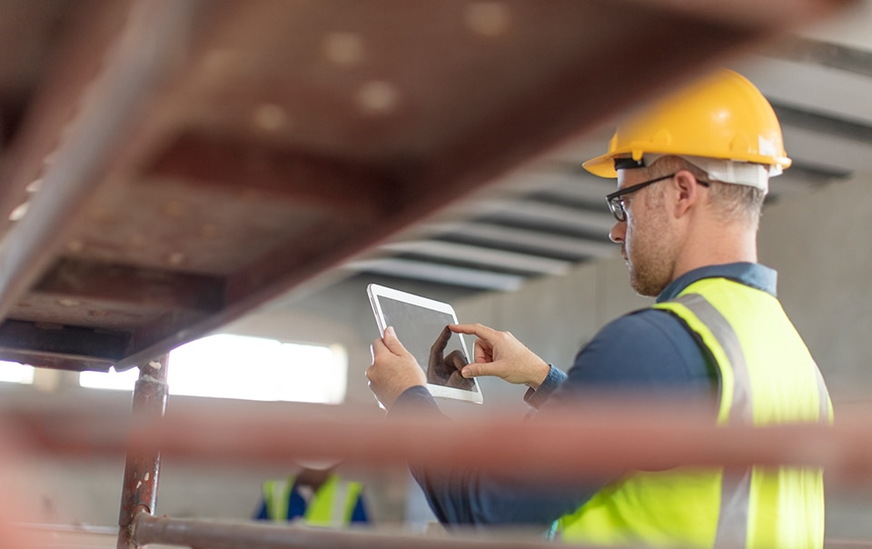 Man at construction site using a digital touchpad