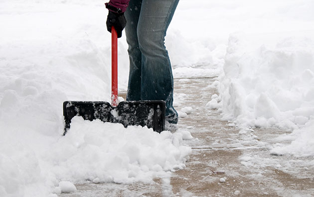 Person shoveling sidewalk to protect against slips, trips and falls during winter