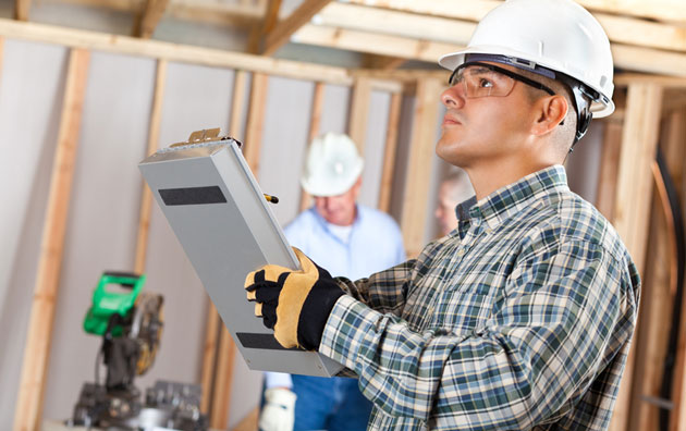 Construction worker assessing construction defects