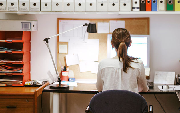Woman sitting ergonomically correct at her desk chair and workstation