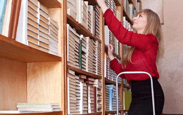 Woman reaching for book on a ladder at work