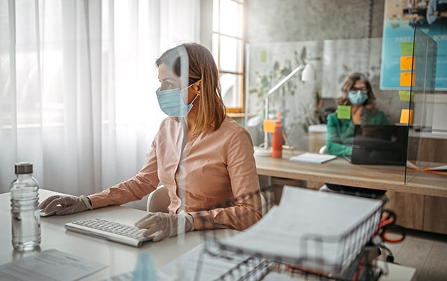 woman with mask on behind glass, working on computer