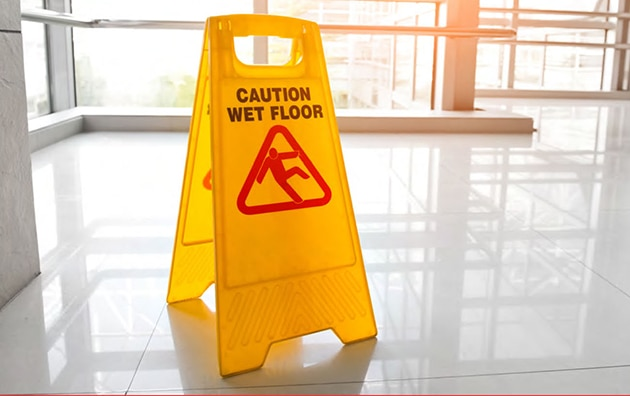 caution wet floor sign in lobby of workplace