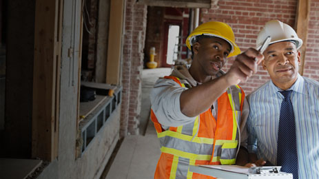 Construction worker and manager looking at construction defects