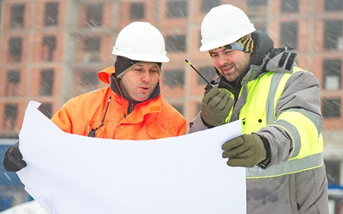 Two workers talking on walkie outside in the snow
