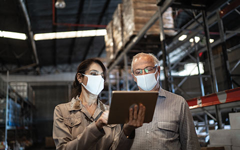 man and woman in masks looking at a tablet in a warehouse. The Right Business Insurance Coverage to Protect Your Company