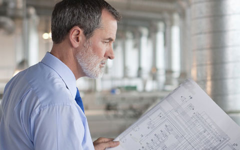 man looking at building design plans, 6 ways to help protect your design firm from professional liability claims