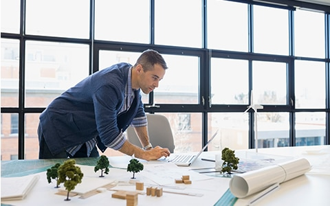 man standing over desk working on laptop, how to choose a professional liability insurance policy for your design firm