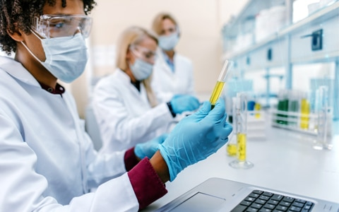 lab technician looking at test tubes and a laptop, Risks Facing Pharmaceutical Companies, From Trial to Commercialization