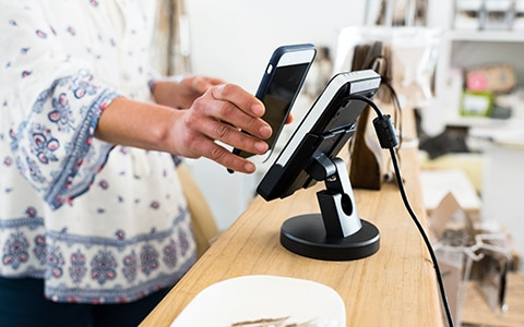 Image of person holding their phone to a retail payment device. Accpepting Mobile Payments for Your Small Business