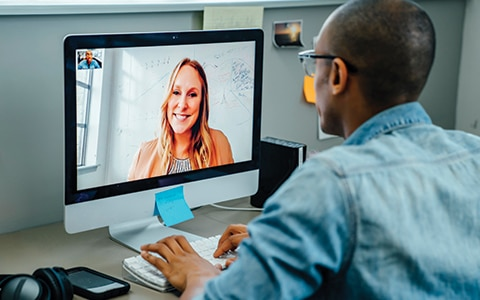 a man on his desktop computer video chatting with a woman