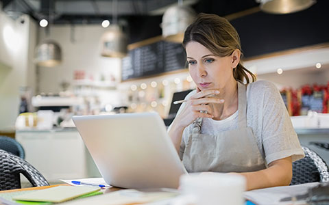 Image of woman in her business looking at a laptop studiously. How to Protect Your Business From a Lawsuit