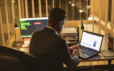 Image of a man sitting at a desk in front of his desktop computer while working on a laptop. 6 Factors Causing Cyber Insurance Rates to Increase