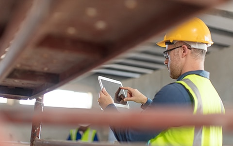 Image of a man in a hard hat working with his tablet on the job. How Interactive Safety Tools Can Help Your Business Spot and Reduce Risks